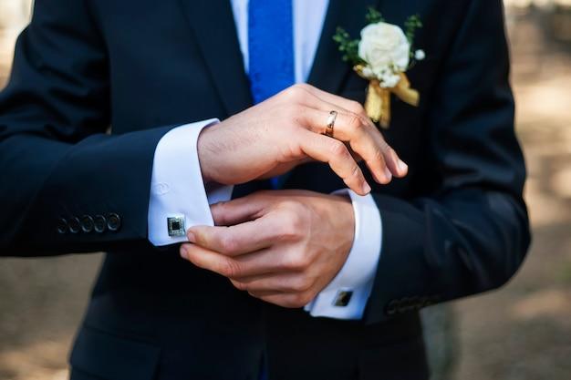 リング、ネクタイ、カフスボタンで優雅な男の手のクローズアップ