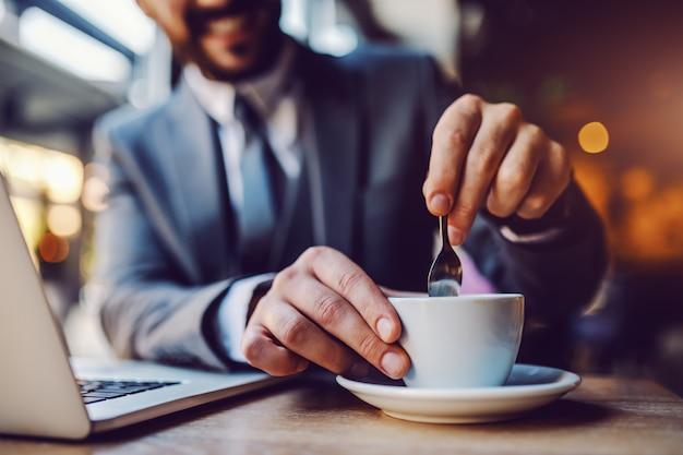 カフェテリアに座りながらコーヒーをかき混ぜるスーツでエレガントなひげを生やした白人実業家のクローズアップ。テーブルの上はラップトップです。