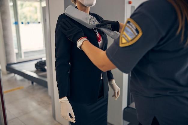 공항 터미널에서 비행하기 전에 보안 검사를 통과하는 우아한 사업가의 닫습니다