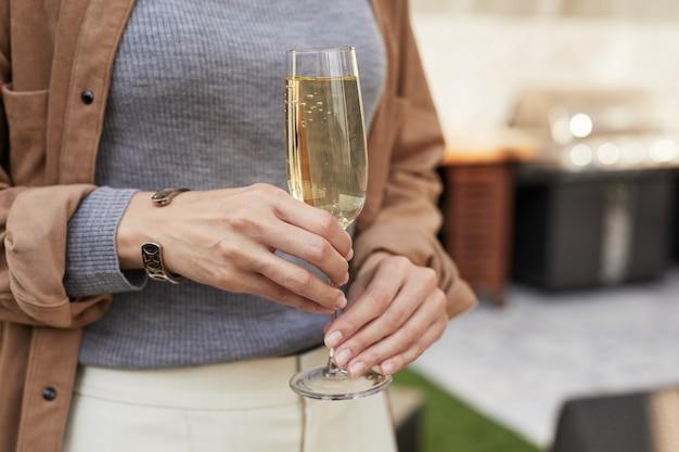 パーティー中に屋外テラスに立っている間シャンパンフルートを保持しているエレガントな女性のクローズアップ、