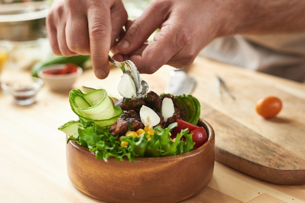 요리사가 준비한 신선한 야채와 고기와 우아한 나무 그릇의 클로즈업