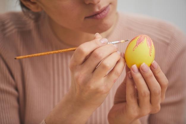 Крупным планом элегантная молодая женщина рисует замысловатый дизайн на пасхальном яйце, копирует пространство