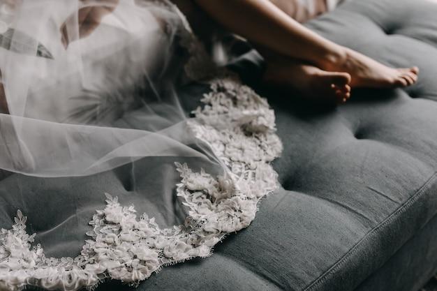 ソファーで横になっている刺繍されたベールのクローズアップ。