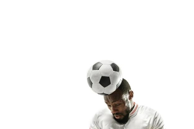 孤立した白い壁に頭でボールを打つサッカーをしている感情的なアフリカ人のクローズアップ。サッカー、スポーツ、顔の表情、人間の感情、健康的なライフスタイルの概念。コピースペース。