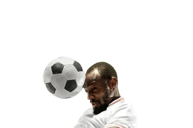 Закройте эмоционального африканского человека, играющего в футбол, бьющего по мячу головой на изолированной белой стене. футбол, спорт, выражение лица, человеческие эмоции, концепция здорового образа жизни. copyspace.
