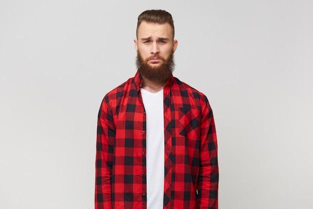 感情的なひげを生やした男のクローズアップは、悲しみ、動揺、欲求不満、不満に見え、シャツを着て、白い背景の上に孤立して立っています。