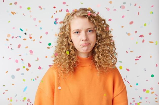 感情的な女の子のクローズアップは、落下する紙吹雪の下で悲しそうに見えます