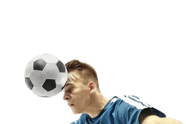孤立した白い背景の上の頭でボールを打つサッカーをしている感情的な男のクローズアップ