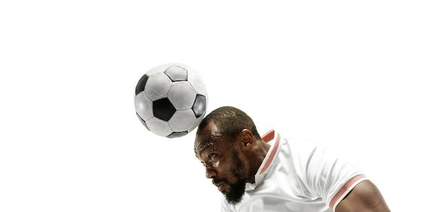 Крупным планом эмоционального человека, играющего в футбол, бьющего по мячу головой на изолированной белой стене