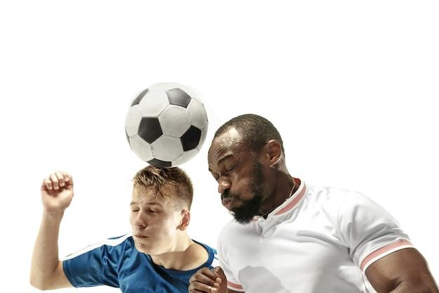 Закройте эмоциональных мужчин, играющих в футбол, ударяя по мячу головой на изолированные на белом фоне. футбол, спорт, выражение лица, концепция человеческих эмоций. copyspace. боритесь за цель.
