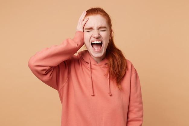 何かに不満を持って大きく口を開けて大声で叫んで目を閉じたポニーテールの感情的な赤毛の女性のクローズアップ