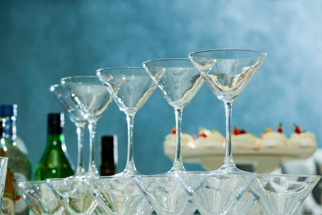 パーティーテーブルのお祝いの空のマティーニグラスのクローズアップ
