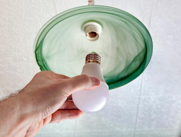 인간의 손에있는 에너지 절약형 led 전구의 클로즈업, 녹색 바닥 유리로 만든 천장 조명기구의 램프 교체.