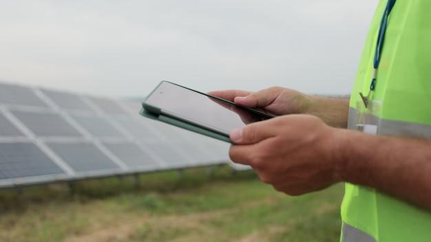 Крупным планом инженер проверяет с планшетным пк работу области фотоэлектрических солнечных панелей. поле солнечных батарей. производство чистой энергии. зеленая энергия.