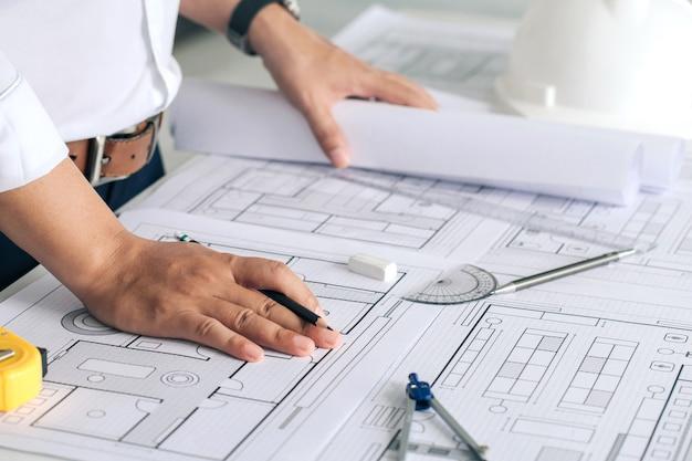 オフィスの建設現場で青写真建築プロジェクトに取り組んでいるエンジニアのクローズアップ