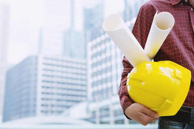 図面計画プロジェクトと安全ヘルメットのロール紙の青写真を保持しているエンジニアリング男性建設労働者のクローズアップ