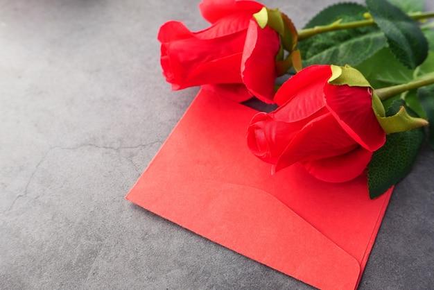黒の背景に封筒とバラの花のクローズアップ。