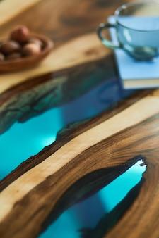 유리와 견과류가 있는 에폭시 나무 커피 테이블을 닫습니다. 세부. 조직.