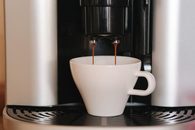 自宅のコーヒーメーカーから注ぐエスプレッソのクローズアップ。アメリカーノ用の白いマグカップ。