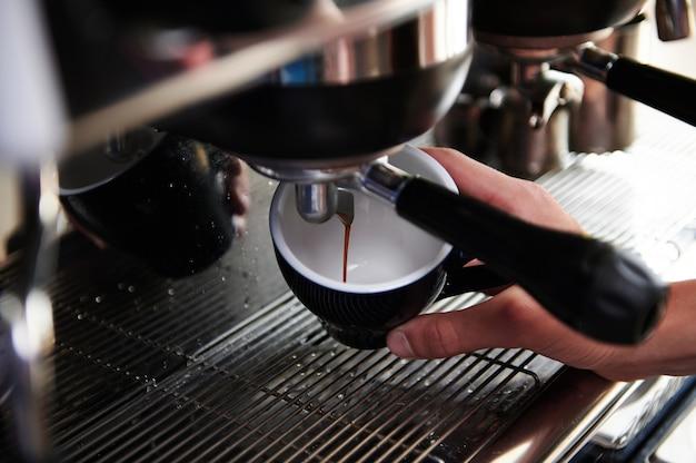 スチームコーヒーマシンからカップに注ぐエスプレッソのクローズアップ。プロのコーヒー醸造。