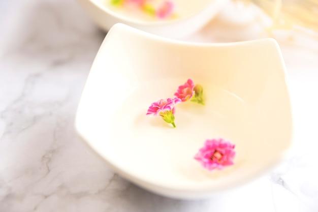 Крупный план эфирного масла с розовыми цветочными лепестками в миске
