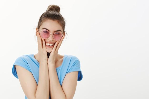 喜びから赤面、賞賛と見ているサングラスで興奮した魅力的な女性のクローズアップ
