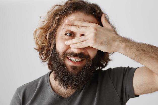 Крупный план возбужденного бородатого мужчины с ближнего востока, любопытно выглядывающего сквозь пальцы