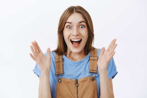 Крупным планом возбужденная красивая девушка хлопает в ладоши и изумленно улыбается, празднуя отличные новости