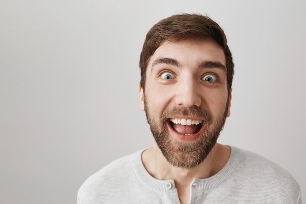 Крупный план возбужденного забавного парня с сумасшедшим выражением лица, улыбаясь
