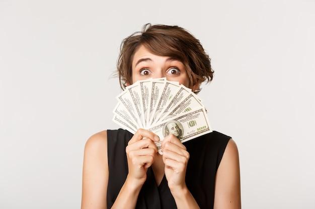 顔の近くでお金を保持している興奮した幸せな女の子のクローズアップ