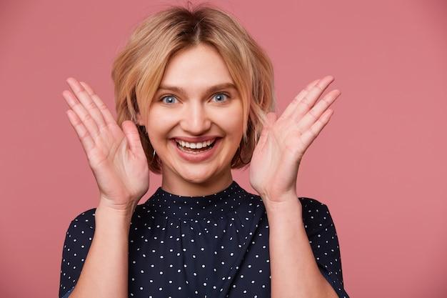 땡땡이 무늬가있는 블라우스를 입은 흥분된 젊은 아름다운 매력적인 금발의 여자를 가까이서 얼굴 근처에 손바닥을 유지하고 분홍색 벽을 통해 긍정적, 미소, 행복을 보여주는 얼굴 표현을 종료했습니다.