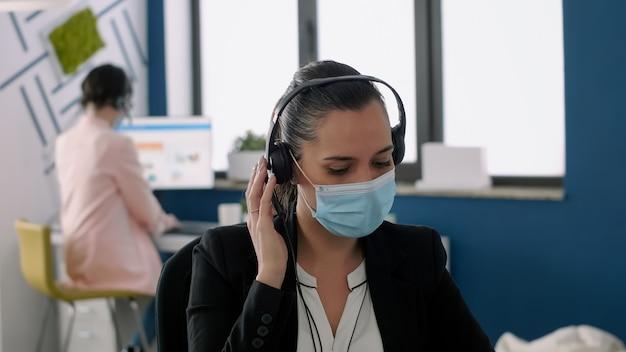코로나바이러스 세계적 대유행 기간 동안 회사 사무실에서 노트북 컴퓨터 작업을 하는 얼굴 마스크와 헤드셋을 갖춘 경영진을 닫습니다. 바이러스 질병을 예방하기 위해 사회적 거리를 유지하는 동료