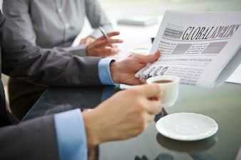 Close-up of executive with a coffee and a newspaper