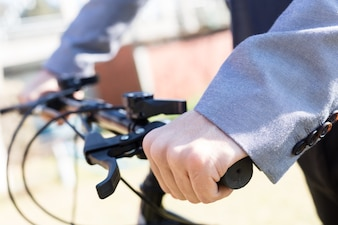 Close-up of executive with hands on handlebars