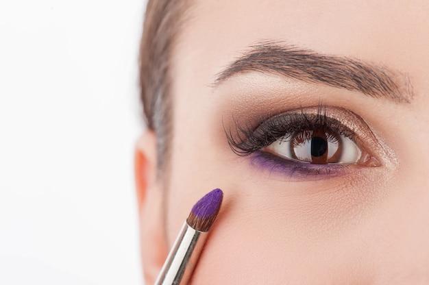 Крупным планом глаза милой молодой женщины, делая макияж в салоне красоты