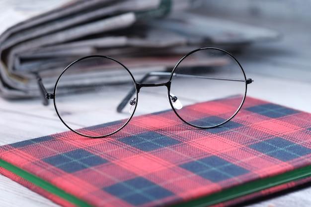 Крупным планом очки и газеты на столе