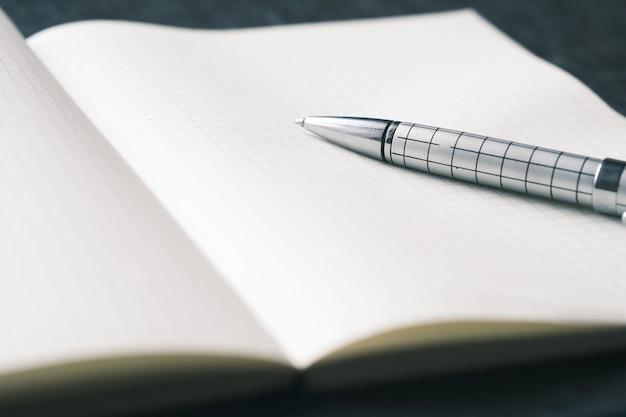 黒の背景にf開いているメモ帳とペンのクローズアップ