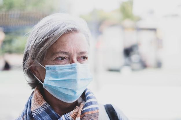 의료용 마스크 예방 코로나바이러스, covi-19 또는 다른 유형의 바이러스를 착용하고 멀리 바라보는 성숙한 여성의 얼굴 클로즈업 - 노인은 심각하게 걱정하고 감염됩니다.