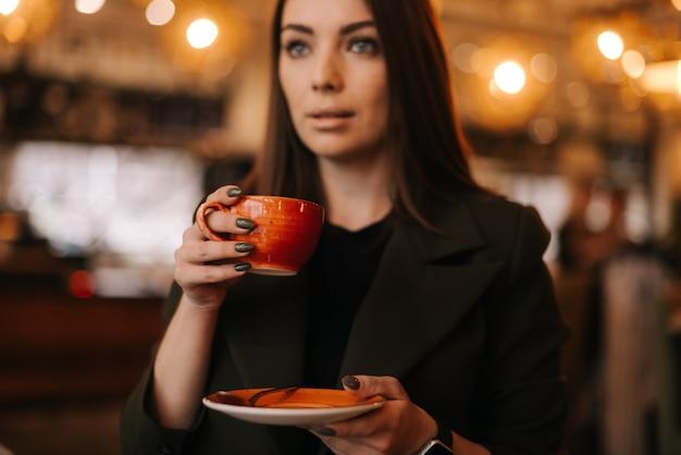 레스토랑에 서 있는 동안 맛있는 뜨거운 커피 한 잔을 손에 들고 있는 젊은 여성의 얼굴 클로즈업