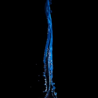 Close-up of falling blue water isolated on black background