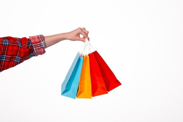 Крупным планом руки famale, держащей маленькие красочные хозяйственные сумки на изолированном белом фоне