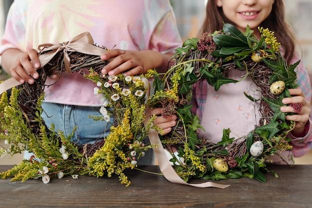 부활절을 위한 꽃과 계란으로 화환을 장식하는 가족의 클로즈업