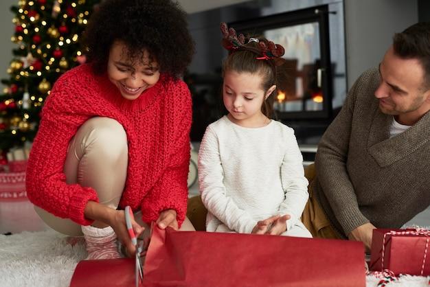 크리스마스 선물을 포장하는 가족의 클로즈업