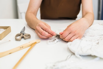 Close-up of fashion designer's hand working on fabric over workdesk