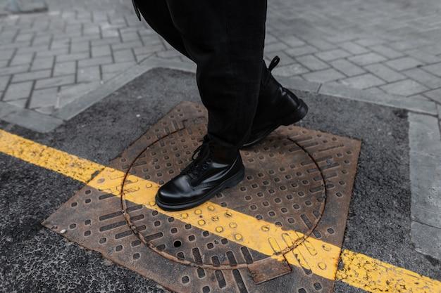 男性の足にファッションレザーの秋春ブーツのクローズアップ。トレンディな靴を履いたヴィンテージジーンズの若い男は、街の鉄のヴィンテージマンホールに立っています。ユースカジュアルスタイル。男性のためのスタイリッシュな靴。