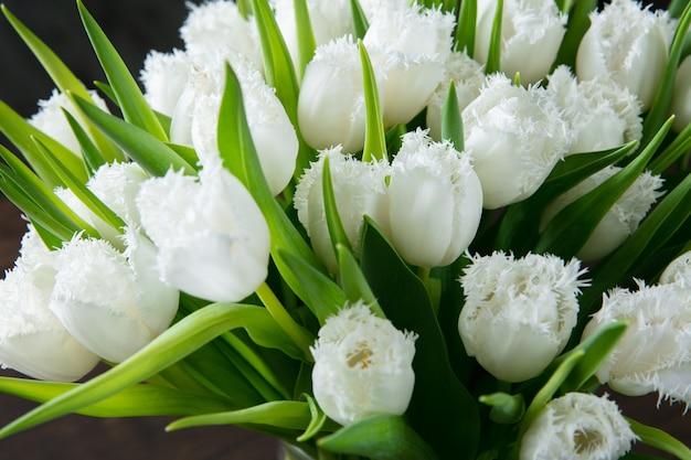 木製の背景にさまざまな花のファッション モダンな花束のクローズ アップ。結婚式、母の日、女性の日に花嫁へのギフト。ロマンティックな春ファッション。やわらかく真っ白なチューリップ。