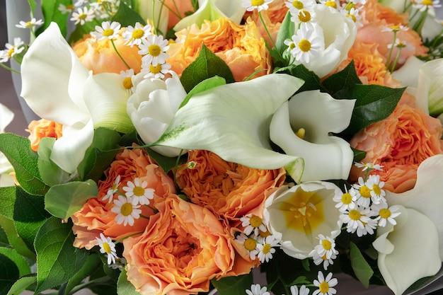 木製の表面にさまざまな花のファッションモダンな花束のクローズアップ。