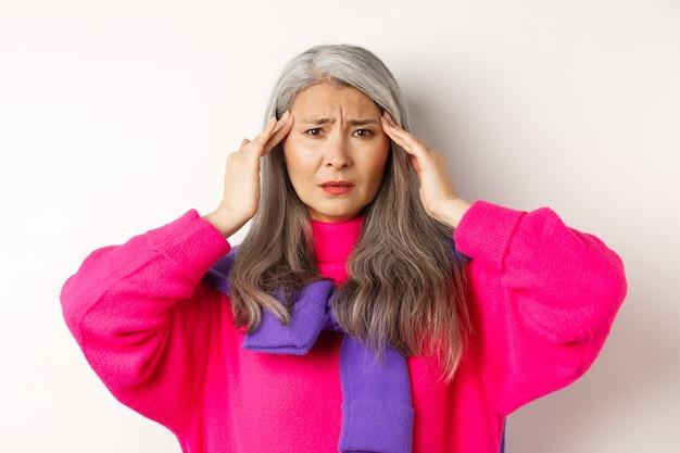 Крупный план модной азиатской пожилой женщины, которая плохо себя чувствует, касается головы и морщится от головной боли, жалуется на мигрень, белый цвет.