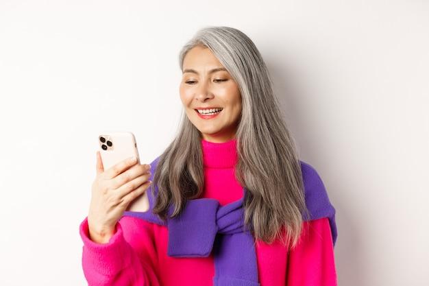 Крупный план модной азиатской старшей женщины, смотрящей на смартфон и чтение сообщения, улыбаясь на мобильный экран, стоя на белом фоне.