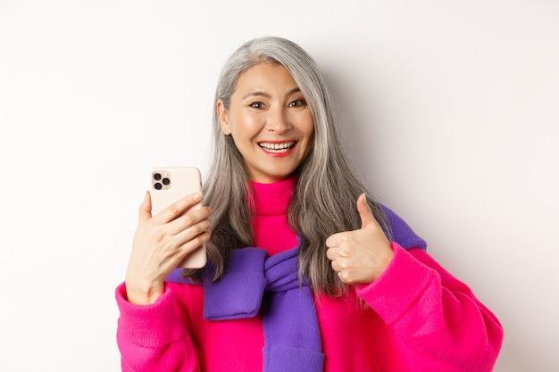 스마트 폰을 사용 하여 엄지 손가락을 보여주는 유행 아시아 고위 여자의 닫고 뭔가 승인, 흰색에 서.
